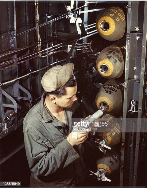 Pfc Lemuel Putty inserts a fuse into a 100 lb bomb already in the bomb bay of a Consolidated B24 Liberator an American heavy bomber England mid1940s