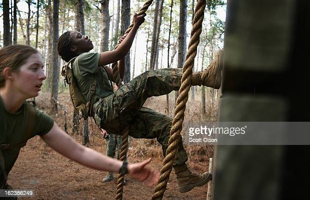 Pfc Michaela Walker and Pfc Britney James climb an obstacle on the Endurance Course during Marine Combat Training on February 20 2013 at Camp Lejeune...