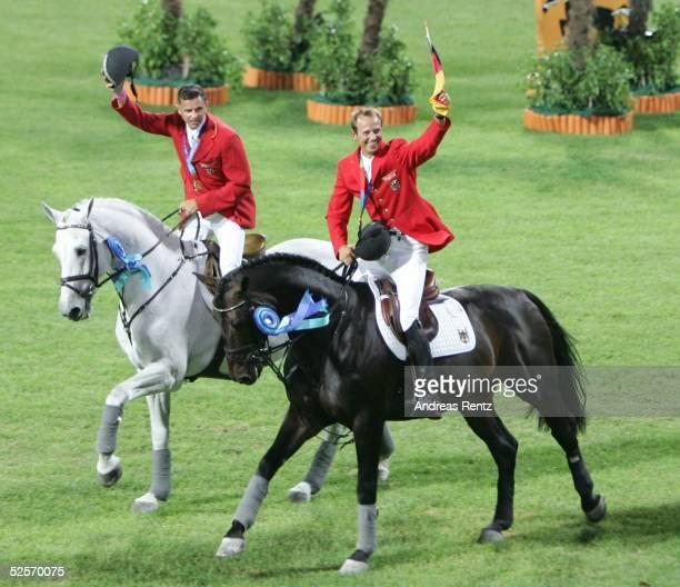 Pferdesport Olympische Spiele Athen 2004 Athen Springen / Mannschaft / Finale Gold fuer Deutschland Otto BECKER und Marco KUTSCHER / GER jubeln den...