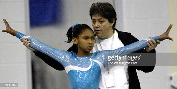pggymnast10 030505 Mark Gail_TWP Prince George's County's Sportplex Gymnastics team coach Grace Ortiz works with MonayHenry before her floor routine...