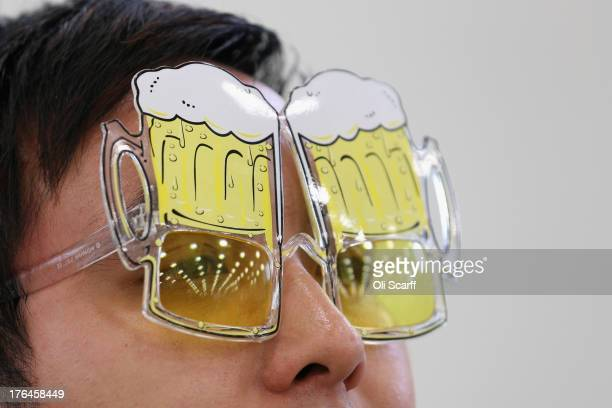 Phai Dip wears novelty beerrelated glasses at the Great British Beer Festival in the Olympia exhibition centre on August 13 2013 in London England...