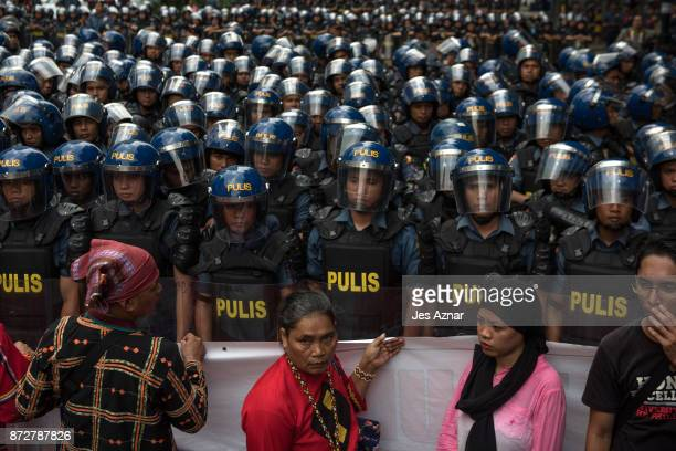 A phalanx of riot police blocks a road as protesters march the streets of Manila a day ahead of US President Trump's arrival on November 11 2017 in...