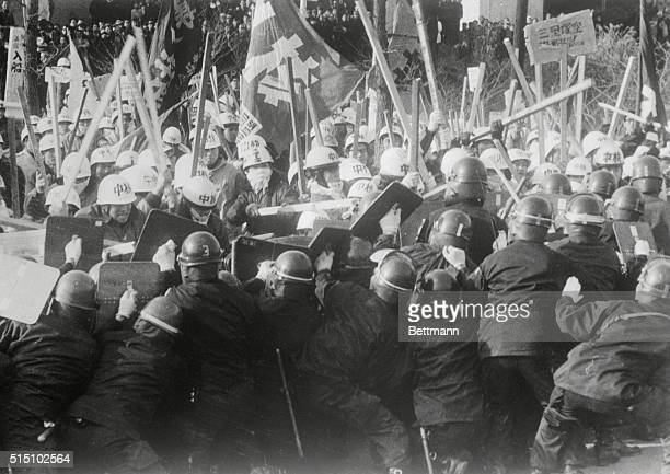 A phalanx of riot policemen marches behind shields at a mob of staffswinging leftist students who are protected from expected blows to the head by...