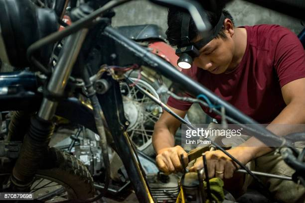 Pham Ngoc Thach a Minsk motorcycle enthusiast turned into professional engineer finetunes his own Minsk motorcycle in preparation for an offroad...