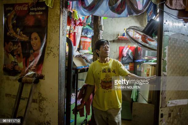 Pham Quoc Cong poses at the door of his twosquaremetre home in Ho Chi Minh City on May 2 2018 The 'microhouse' dwellings are dotted throughout...