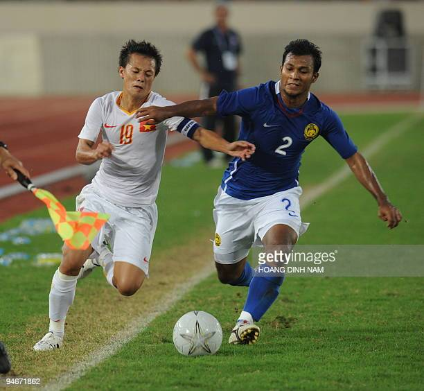 Pham Thanh Luong of Vietnam fights for the ball with Matabu Mohd Sabre of Malaysia during their men's football final at the 25th Southeast Asian...