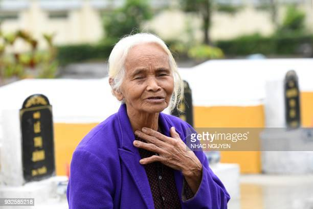 Pham Thi Thuan a survivor of the My Lai massacre gestures while visiting the mass grave in Son My village in Quang Ngai province on March 15 2018 The...