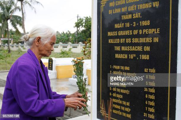Pham Thi Thuan a survivor of the My Lai massacre places flowers at the mass grave in Son My village in Quang Ngai province on March 15 2018 The...