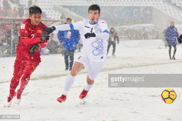 Pham Xuan Manh of Vietnam and Akramjon Komilov of Uzbekistan compete for the ball during the AFC U23 Championship China 2018 final match between...