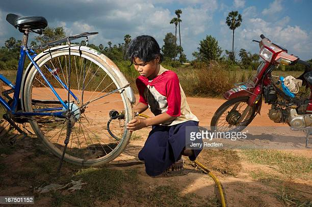 Phan Champa whose mother says she is seven fills bike and moto tires will air in front of her family's house She is also in charge of caring for her...