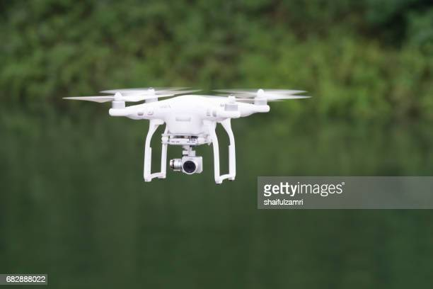 dji phantom 3 standard quad-copter flying into royal belum rainforest national park - helicopter photos stock pictures, royalty-free photos & images