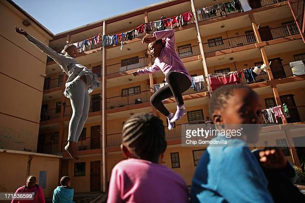 Phaphama Nxumalo and Natasha Mbatha members of the Alexandra Trampoline Club practices in an alleyway between apartment blocks June 26 2013 in...