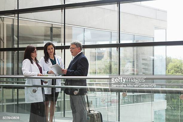 Pharmaceutical representative and two female doctors looking at digital tablet