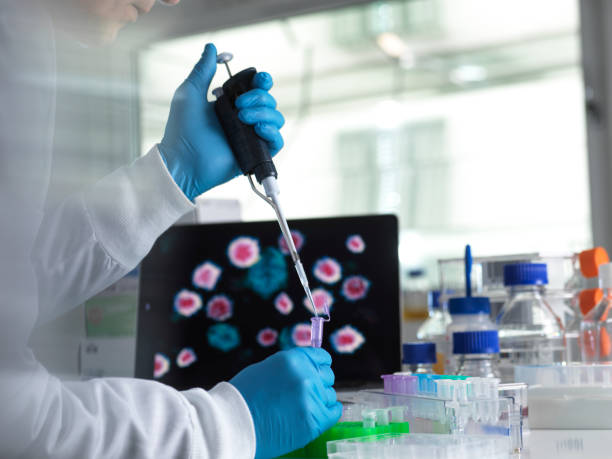 pharmaceutical research into infectious disease and pandemics, scientist pipetting a sample of a new drug formula into a vial during a clinical trial with the infectious disease on the computer screen - coronavirus stock pictures, royalty-free photos & images