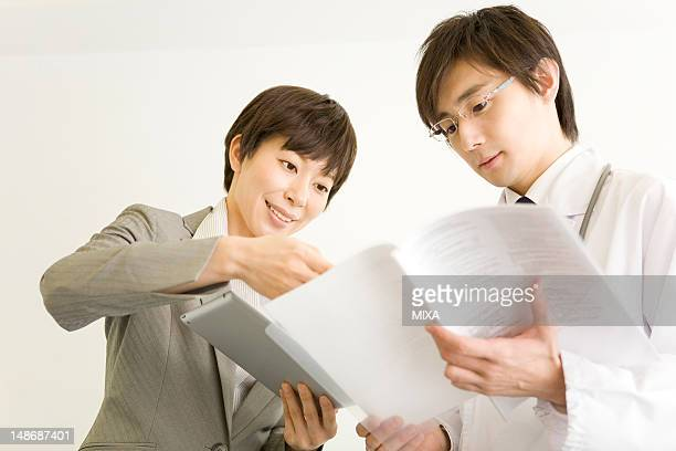 Pharmaceutical sales representative showing file to doctor