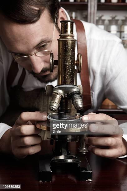 Pharmacist adjusting microscope