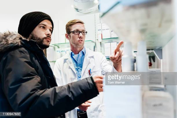 pharmacist advising customer on healthcare - warm clothing stock pictures, royalty-free photos & images