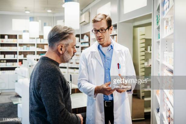 pharmacist advising customer on medicine instructions - pharmacy stock pictures, royalty-free photos & images
