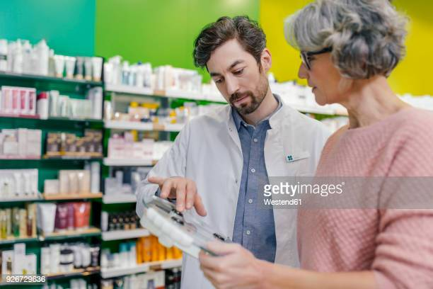 Pharmacist advising customer with sclaes in pharmacy