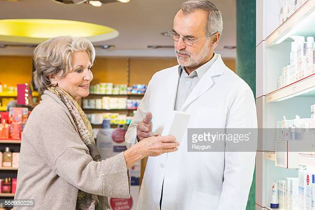 Pharmacist advising senior woman on medicine in pharmacy