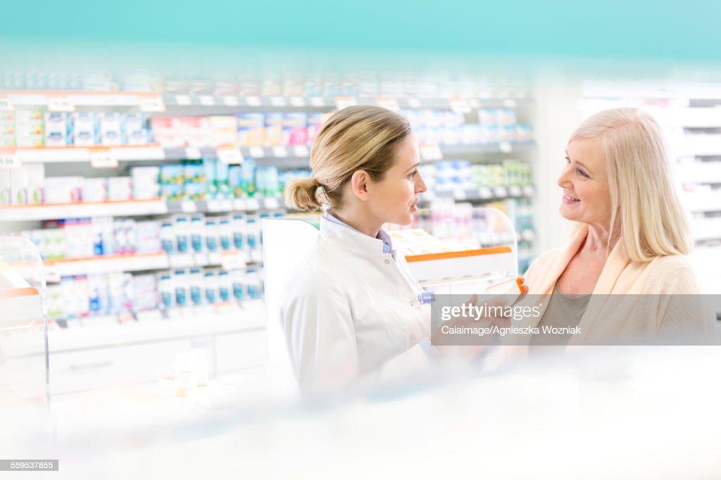 Pharmacist and customer talking in pharmacy : Stock Photo