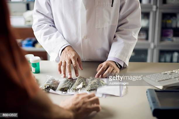 pharmacist and customer with medical marijuana - medical cannabis stock photos and pictures