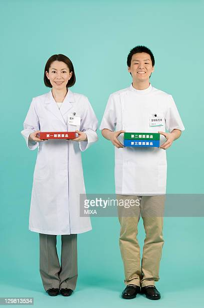 Pharmacist and Registered Vendor of Drugstore Holding Boxes of Classification of OTC Drugs