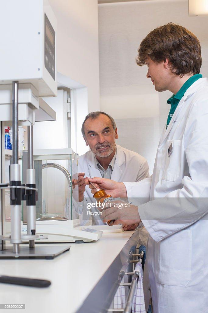 Pharmacist And Trainee Mixing Medicine In Pharmacy Stock Photo ...
