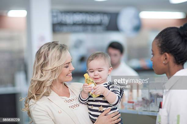 Pharmacist assisting client with baby in drugstore