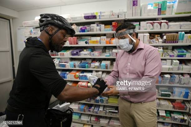 Pharmacist at a Boots Pharmacy, in PPE including a full face mask as a precautionary measure against COVID-19, passes a completed prescription to...