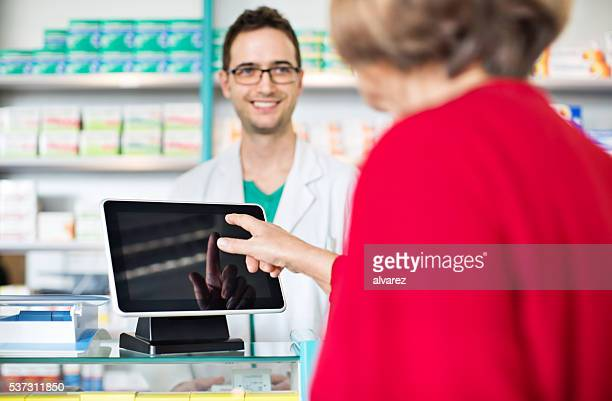 Pharmacist at checkout counter with customer paying through digital tablet