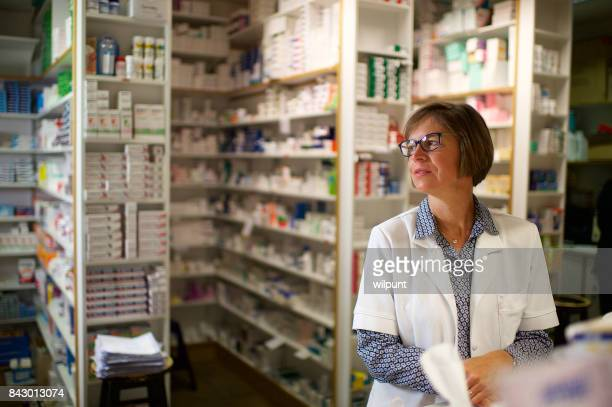 pharmacist behind pharmacy counter looking sideways - generic drug stock pictures, royalty-free photos & images