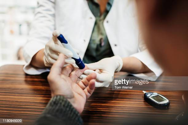 pharmacist checking customer's blood sugar levels - diabetes stock pictures, royalty-free photos & images