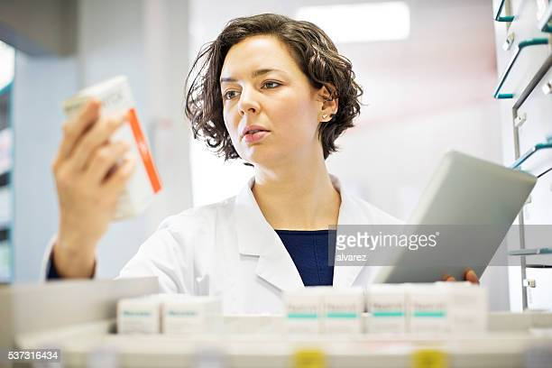 Pharmacist checking medication inventory at pharmacy store