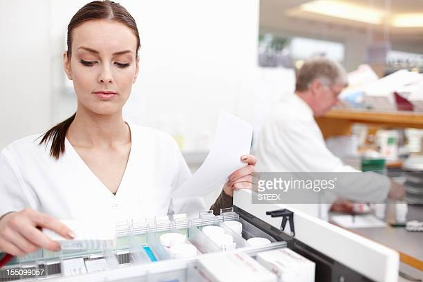Pharmacist checking medicine with colleague in background