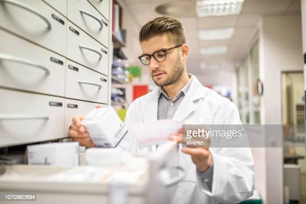 apotheker überprüfen arzneimittel auf rack - verschreibungspflichtiges medikament stock-fotos und bilder