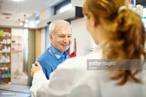 Consolando a hombre mayor en la tienda del farmacéutico