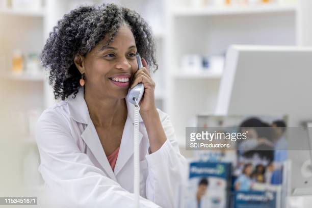 pharmacist consults computer records for patient - one mature woman only stock pictures, royalty-free photos & images