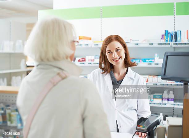 Pharmacist conversing with customer