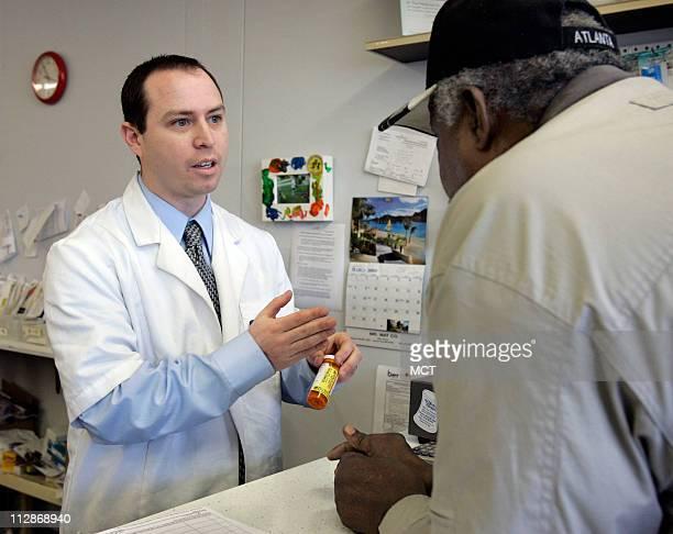 Pharmacist Daniel Reif, left, talks with Willie Randle Sr. About a prescription, March 4 at The Medicine Shoppe, in Kansas City, Kansas.