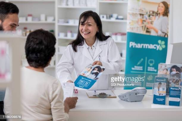 pharmacist discusses flu vaccine with customers - pamphlet stock pictures, royalty-free photos & images