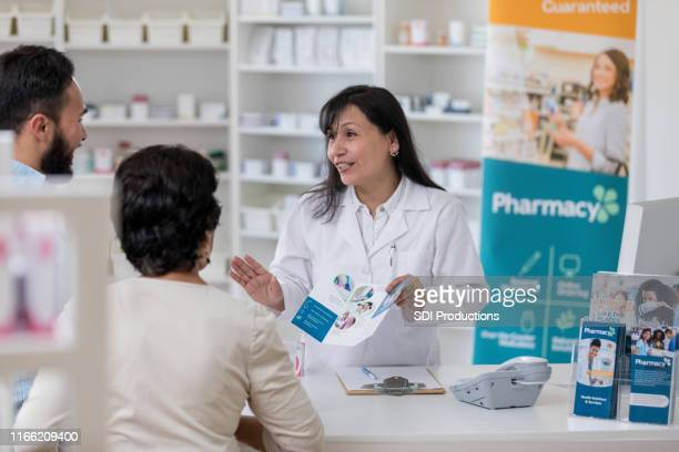 pharmacist discusses pharmacy services - flyer leaflet stock pictures, royalty-free photos & images