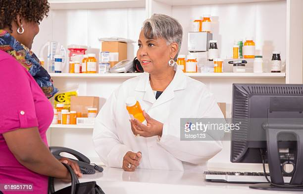Pharmacist discusses prescription medication with customer at pharmacy.