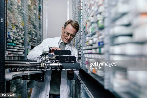 pharmacist examining commissioning machine in pharmacy - medikament stock-fotos und bilder