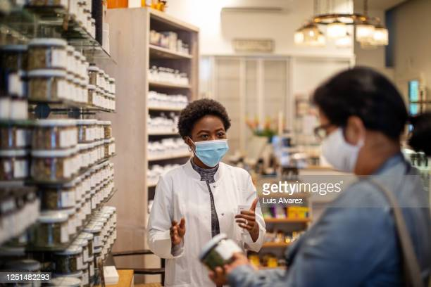 pharmacist explaining medication to female customer - essential workers stock pictures, royalty-free photos & images