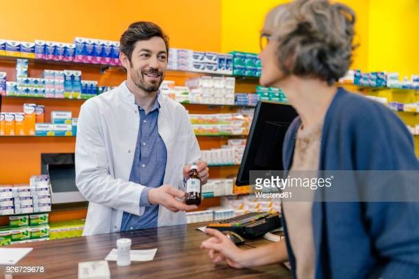Pharmacist explaining medicine to customer in pharmacy