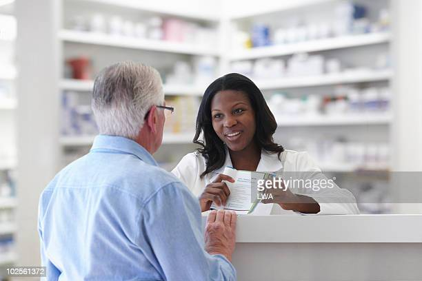 pharmacist explaining pamphlet to senior - pamphlet stock pictures, royalty-free photos & images