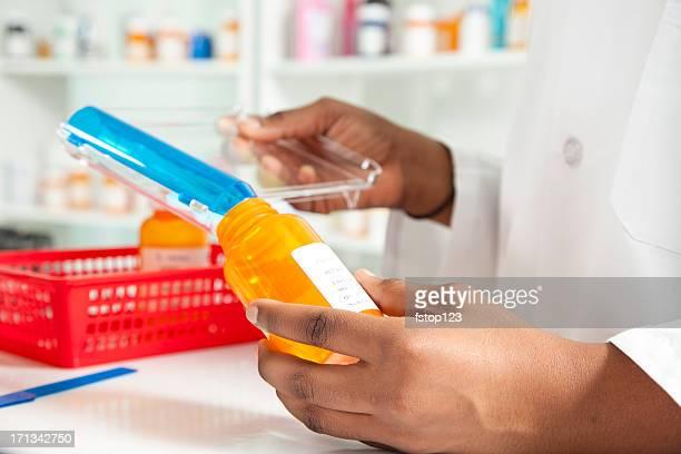 Pharmacist filling bottle for a prescription