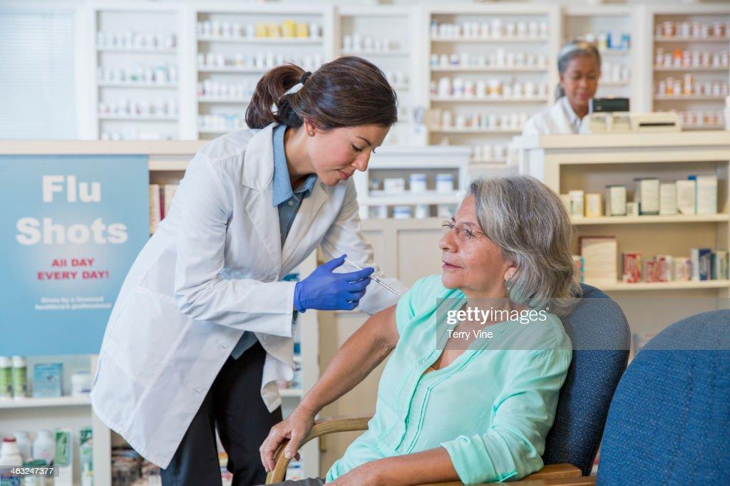 Pharmacist giving customer flu shot : Stock Photo