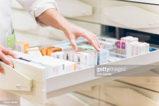 pharmacist hand taking medication from drawer - medikament stock-fotos und bilder